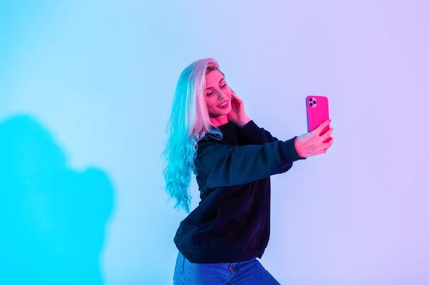 Felice bella ragazza sorridente in felpa con cappuccio nera con jeans scatta foto di se stessa al telefono in studio su uno sfondo rosa blu. la donna graziosa fa il selfie sullo smartphone