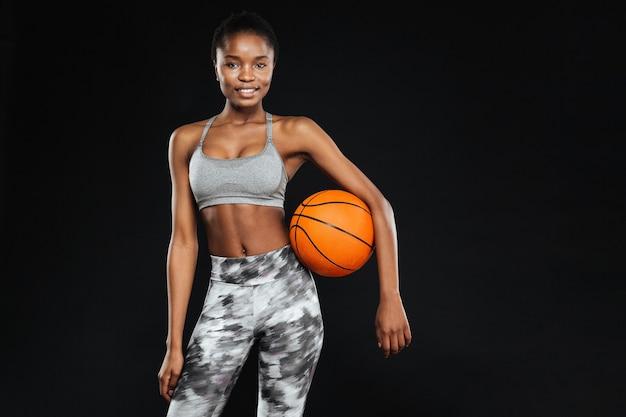 Felice bella donna sportiva che tiene palla isolata sul muro nero