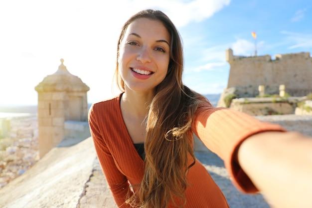 Felice bella donna turistica che cattura foto selfie ad alicante, in spagna