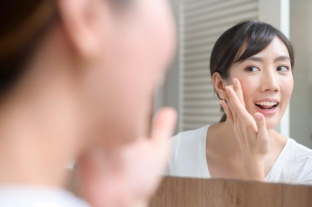 Una bella donna felice che applica crema idratante sul viso, cura della pelle e concetto di trattamento