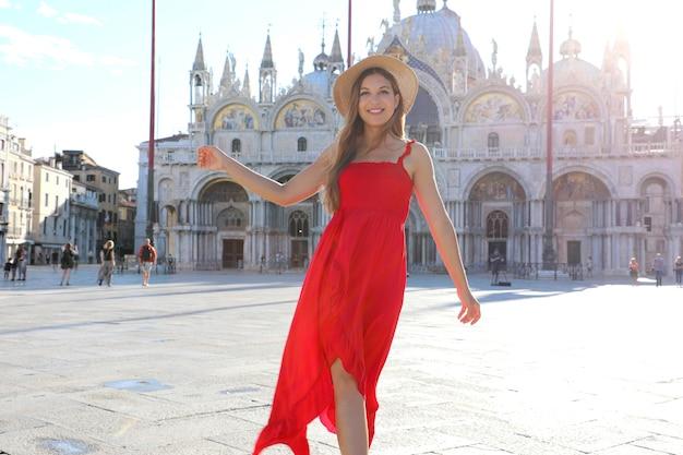 Bella donna felice in vestito rosso elegante ballando in piazza san marco a venezia, italia