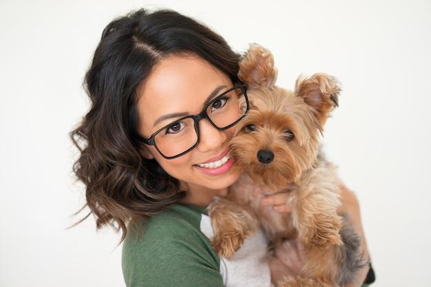 Bella donna felice che abbraccia yorkshire terrier