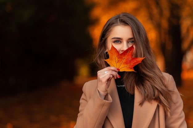 Felice bella donna in un cappotto beige alla moda e un maglione si copre il viso con una foglia autunnale colorata in un parco con fogliame autunnale arancione. spazio per il testo