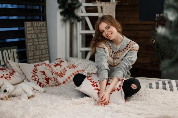La bella donna felice in maglione lavorato a maglia alla moda abbraccia un cuscino che si siede sul letto