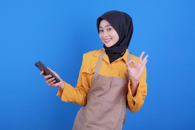 Bella donna felice che tiene telefono e che dice gesto giusto