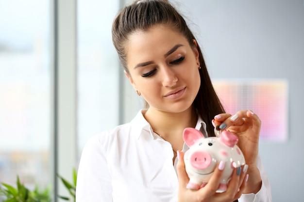 Bella donna felice che presenta moneta nel porcellino salvadanaio