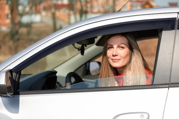 Bella donna felice che osserva da una macchina di guida
