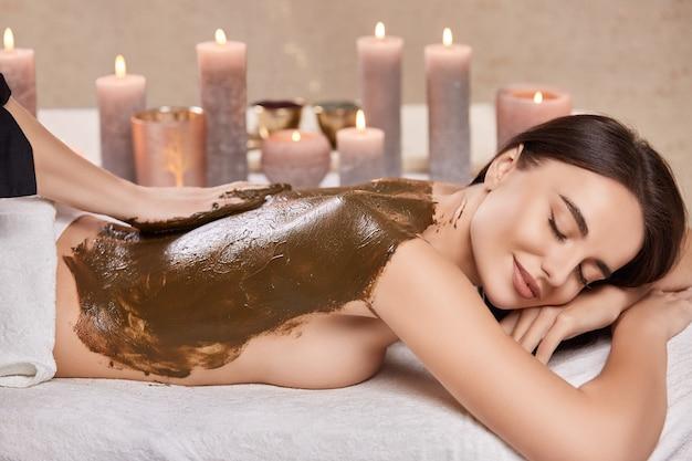 Donna felice e bella riceve la maschera di cacao per il suo corpo nella spa