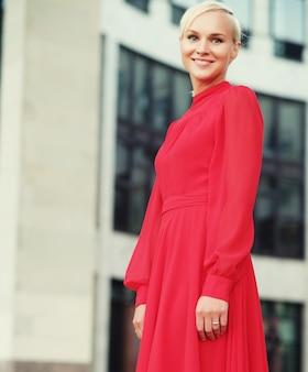 Felice bella donna in abito estivo rosso che cammina e corre sorridente gioiosa e allegra. giorno d'estate.