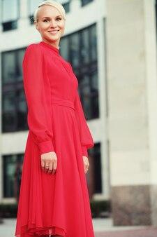 Felice bella donna in abito estivo rosso a piedi e in esecuzione sorridente gioioso e allegro. giorno d'estate.