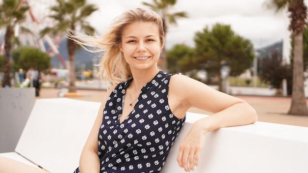 Felice bella donna seduta e guardando la spiaggia durante le sue vacanze, ora legale