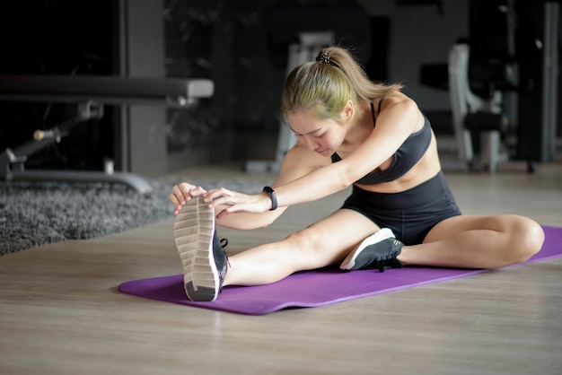 Una bella donna felice in abiti sportivi sta facendo stretching e riscaldamento sulla stuoia prima del suo allenamento in palestra, fitness e concetto di salute.
