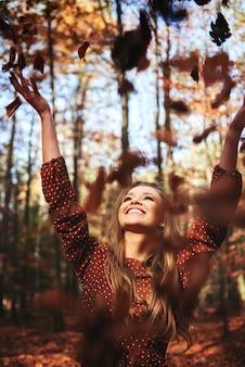 Felice bella donna che getta foglie d'autunno nella foresta