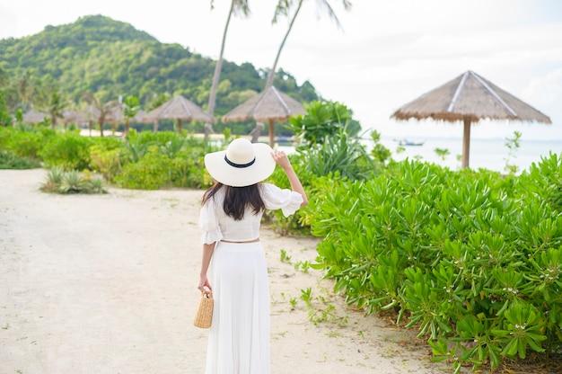 Una bella donna felice in vestito bianco che gode e che si rilassa sulla spiaggia, l'estate e il concetto di vacanze