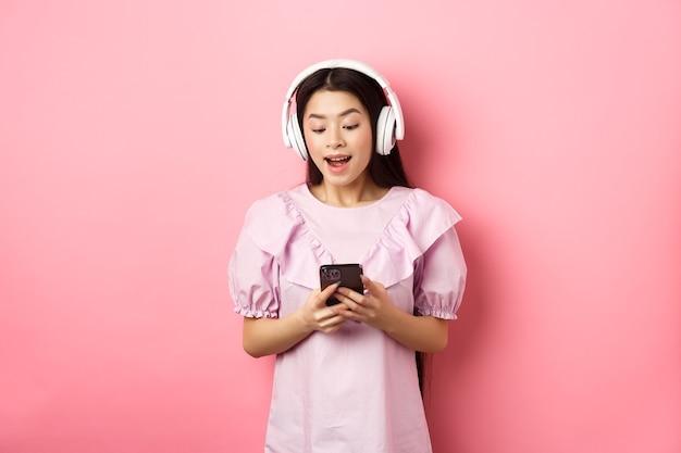 Bella donna felice in cuffie senza fili guardando video su smartphone, guardando il telefono divertito, in piedi su sfondo rosa.