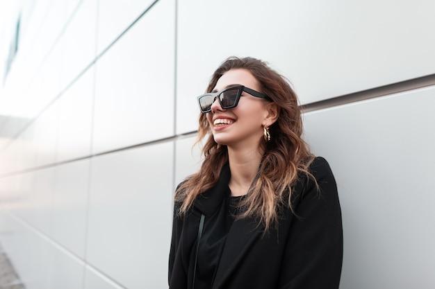 Bella donna felice con il sorriso in vestiti neri di modo