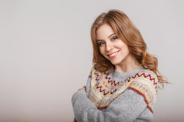 Bella donna felice con un sorriso in un maglione vintage di moda su uno sfondo grigio