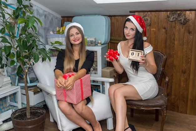 Donne felici e belle con scatole regalo in studio