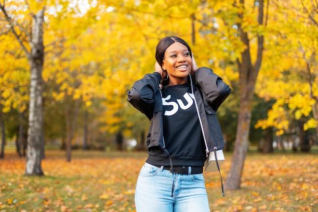 Felice bella giovane donna afroamericana con un sorriso in abbigliamento casual con giacca e jeans nel parco autunnale con fogliame dorato colorato