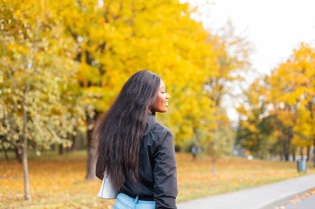 Felice bella giovane donna afroamericana con un sorriso in abiti casual alla moda che cammina nel parco autunnale con fogliame giallo colorato brillante