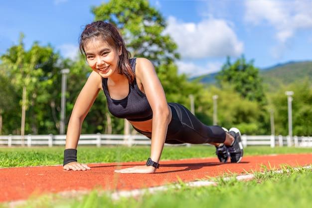 Felice bella giovane donna asiatica facendo esercizio di spinta verso l'alto al mattino in una pista da corsa in una luminosa giornata di sole