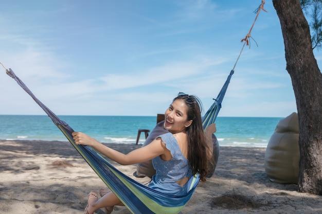 Bella giovane donna asiatica felice che si siede sull'amaca in spiaggia in vacanza