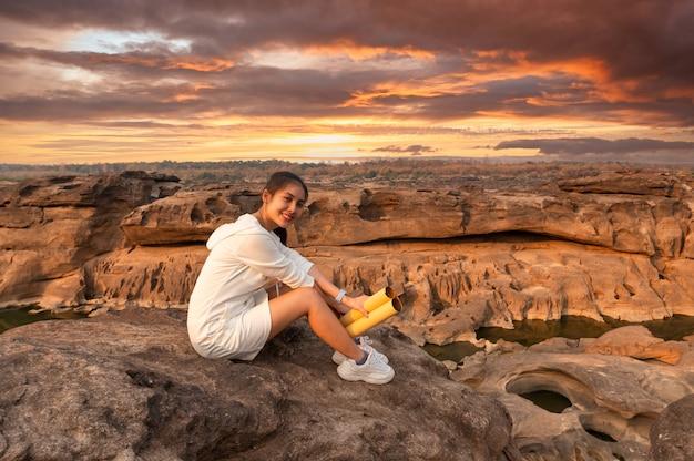 Viaggiatore felice bella giovane donna asiatica con mappa cartacea che si siede sulla scogliera di roccia nel grand canyon della thailandia al tramonto