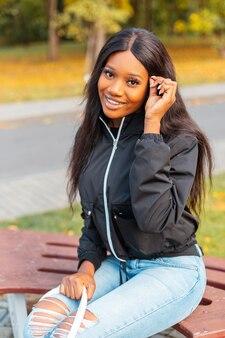 Felice bella giovane donna di colore con un sorriso in una giacca casual alla moda con jeans si siede su una panchina in un parco autunnale con fogliame giallo