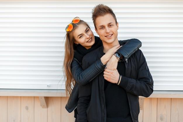 Belle giovani coppie felici in vestiti alla moda di modo vicino al muro bianco