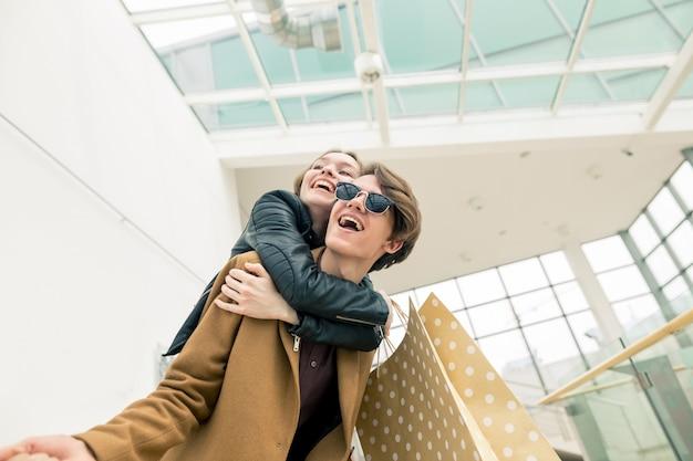 Bei giovani sacchetti della spesa felici della tenuta delle coppie mentre stando nel centro commerciale.