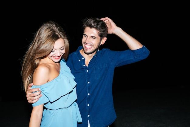 Felice bella giovane coppia in piedi e abbracciata di notte sulla spiaggia