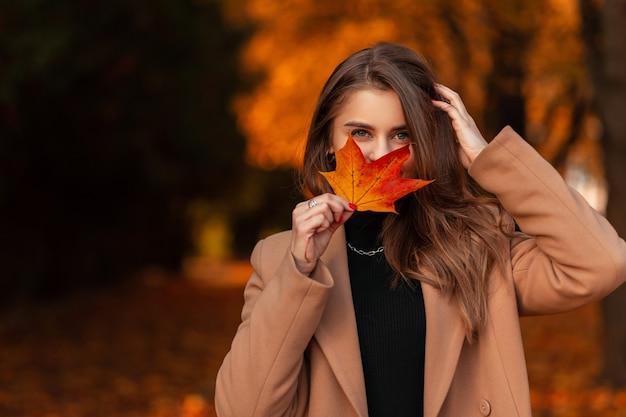 Felice bella ragazza in cappotto alla moda si copre il viso con foglie autunnali colorate nel parco autunnale dorato. vacanze autunnali