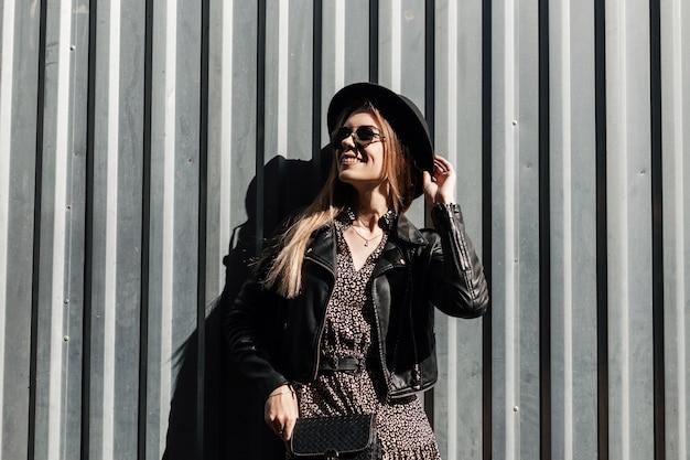 Modello felice bella ragazza con un sorriso carino con occhiali da sole alla moda e un cappello in una giacca di pelle nera e un abito vintage si trova vicino a un muro di metallo in una giornata di sole