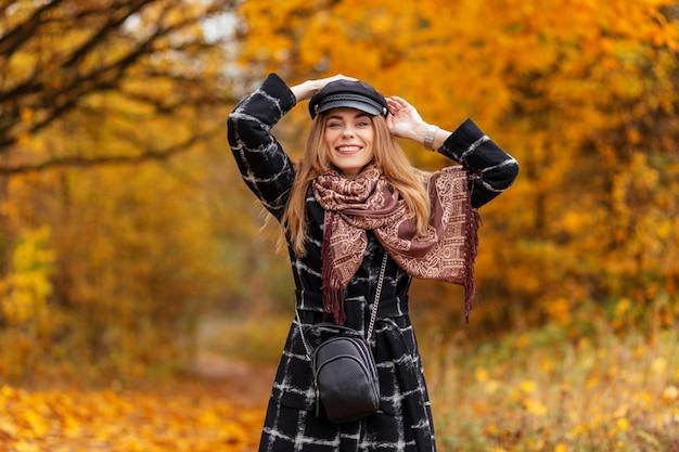 Felice bella ragazza con un sorriso di bellezza in abiti di moda e un cappotto con una sciarpa e un cappello cammina nella foresta autunnale con fogliame autunnale giallo
