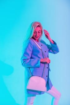 Bella ragazza felice con capelli biondi in modo elegante con un blazer blu e una borsa bianca alla moda in studio con un color pastello