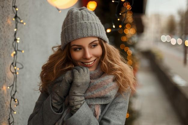 Bella ragazza giovane felice con un sorriso eccellente in vestiti di maglieria in un cappotto grigio e un berretto lavorato a maglia sulla strada vicino alle luci