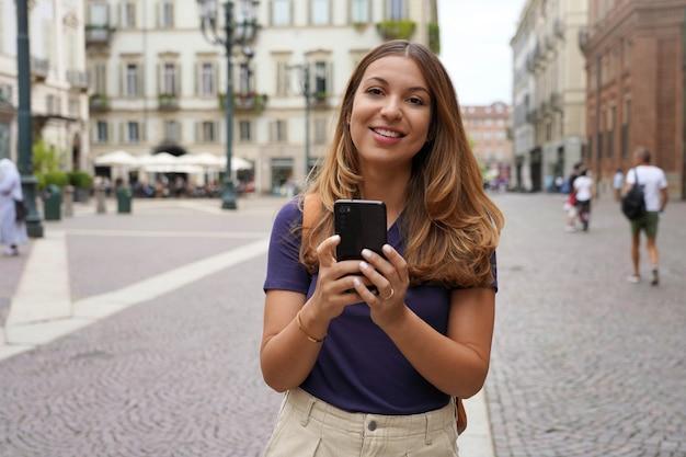 Felice bella giovane studentessa che guarda l'obbiettivo e che tiene il telefono cellulare all'aperto con sfondo sfocato della città. tecnologia della gente di stile di vita della città.