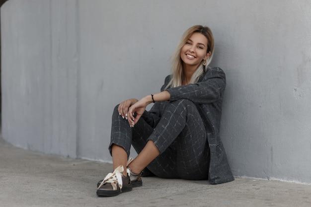 Felice bella giovane ragazza modello alla moda con un sorriso in un abito vintage grigio con una giacca alla moda e pantaloni sorridenti e seduti vicino al muro
