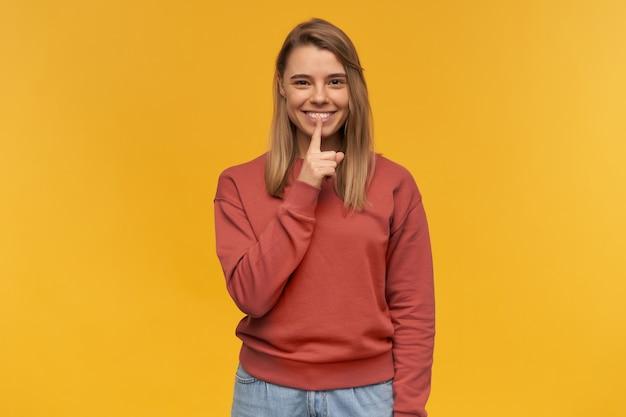 Bella giovane donna felice in abbigliamento casual che sorride e mostra il gesto di silenzio dal dito sopra la parete gialla.