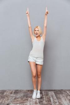 Felice bella giovane donna che celebra il successo e punta verso l'alto sul muro grigio