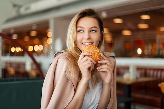 Bella giovane donna felice che mangia un hamburger al chiuso