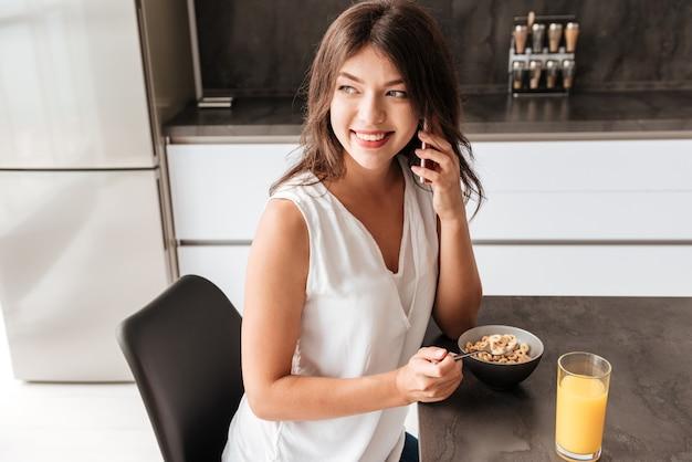 Felice bella giovane donna che fa colazione e parla al cellulare in cucina