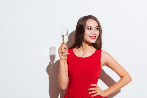 Felice bella giovane donna in abito rosso in piedi e bevendo champagne su sfondo bianco