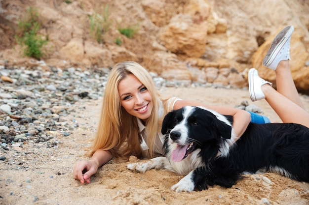 Bella giovane donna felice che si rilassa con il cane sulla spiaggia