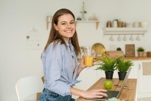 Felice bella giovane donna seduta al tavolo a casa, lavorando in un computer portatile e bevendo delizioso succo d'arancia, guardando la telecamera. lavorare e studiare da casa in condizioni di quarantena.