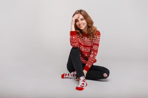 Felice bella giovane donna sorridente in maglione vintage rosso lavorato a maglia con stampa seduta sul pavimento