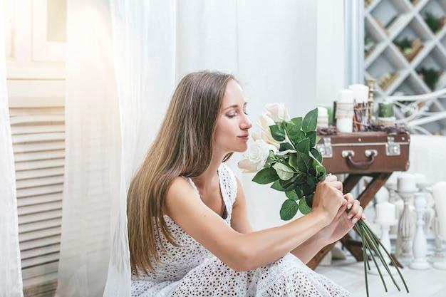 Bella giovane donna felice in un vestito bianco a casa con un mazzo di fiori bianchi