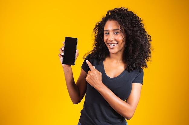 Felice bella giovane donna con capelli afro che tiene il telefono cellulare a schermo vuoto e punta il dito su sfondo giallo.