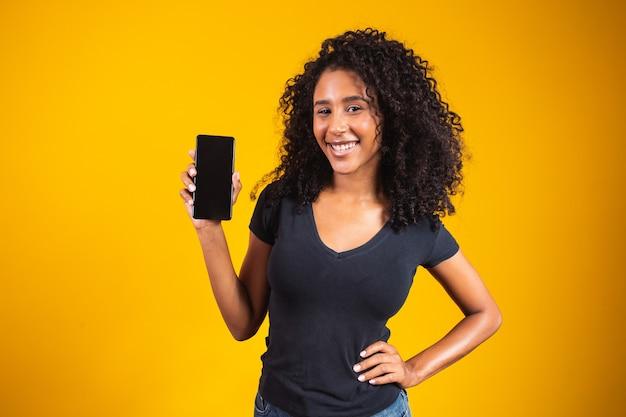 Bella giovane donna felice con capelli afro che tiene telefono cellulare schermo vuoto su sfondo giallo.