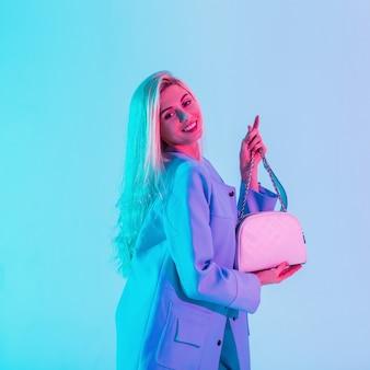 Felice bella giovane donna con un sorriso carino in una giacca blu brillante alla moda con una borsa elegante in studio su luce rosa al neon